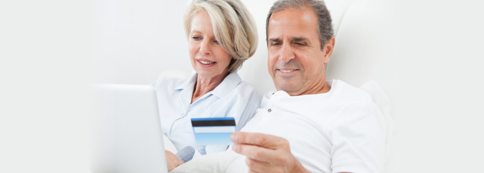 elderly man holding insurance card with his wife